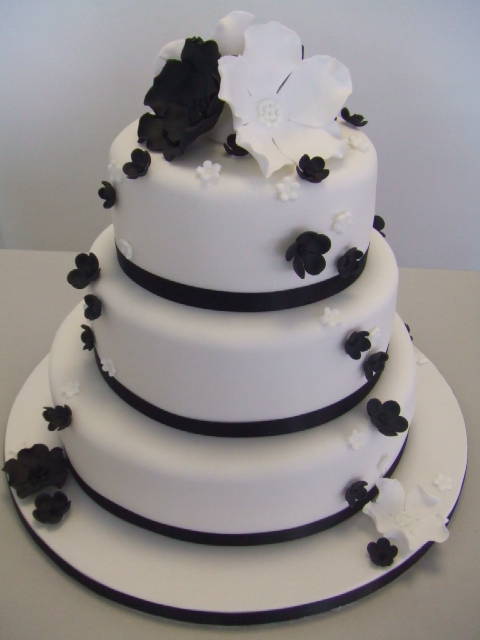 Three tier white cake with black ribbons and black and white flowers