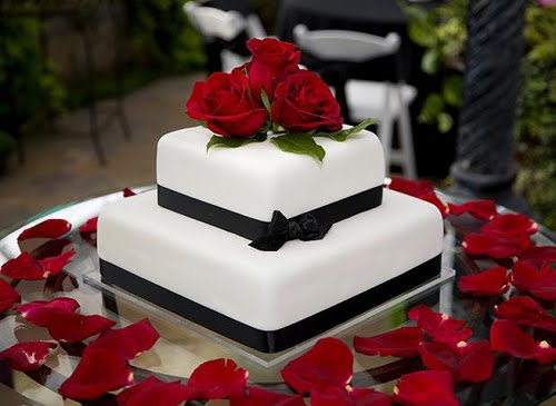 Two tier white square cake with black ribbons around tiers and red roses on