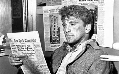 Personagem de Kirk Douglas lendo um jornal, em cena de 'A Montanha dos Sete Abutres'