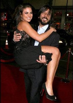 Daniel Sadek carries actress Nadia Bjorlin on the red carpet at premier of movie Redline, in LA on April 12, 2007