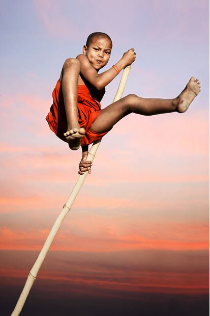 A novice monk bravely flies through the air on a piece of bamboo in Mruak U, Myanmar