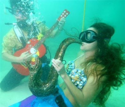 Divers and snorkelers pretending to play on fake instruments