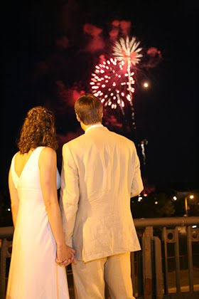 Couple holding hands watching fireworks during their wedding at the Harbor Lights room