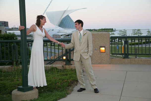 John and Ellie holding hands outside with the Calatrava Art Museum as a backdrop