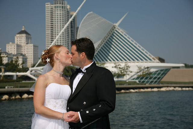 Bridal couple kissing before wedding in front of Calatrava by Milwaukee lakefront