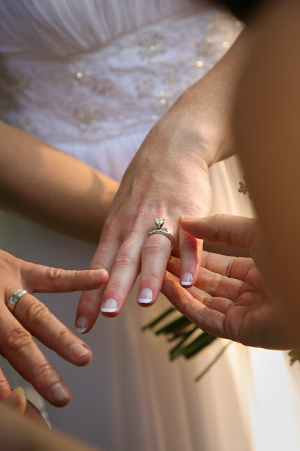 Guests looking at wedding ring on bride's hand