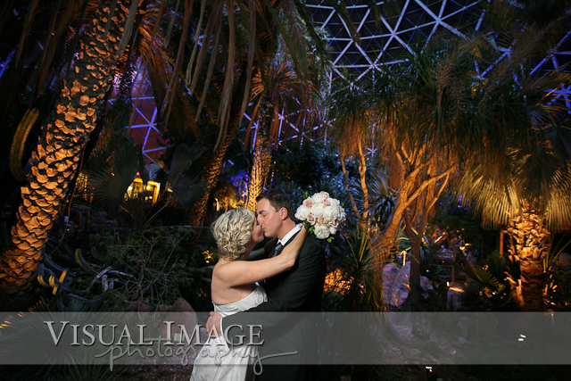 Bride and groom kissing in arid dome during wedding at Mitchell Park Domes