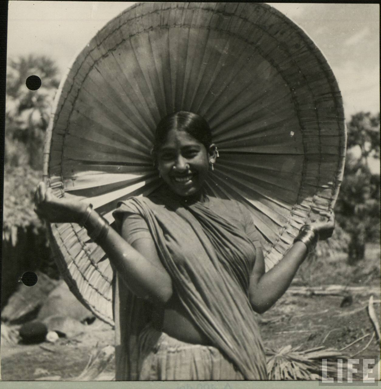 An Indian Lady is Holding a Canopy