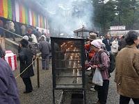 金堂前で蝋燭に灯りをいれ礼拝する人たち