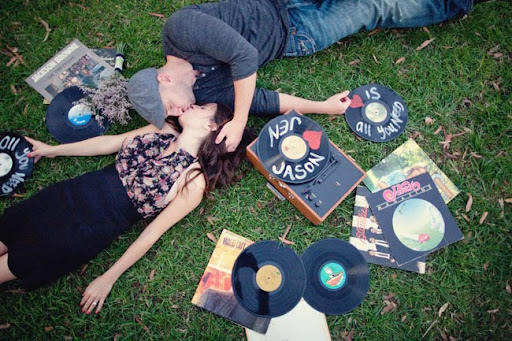 couple kissing with records on grass record player