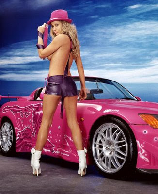 Hot girls pose in front of sports cars. Why? Because they can and they get