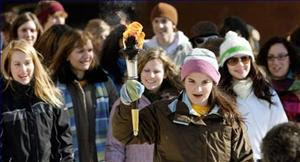 St. Joseph-Scollard Hall Catholic Secondary School student Julie Perrotta, 16, holds a torch during a walk from city hall to her school, Wednesday, to raise awareness about organ and tissue donation. Photo by Paul Chivers.