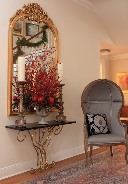 Porta Romano table with a domed wing chair and an antique mirror.