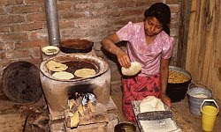 A color photo of a Central-American woman making tortillas circa 1990.