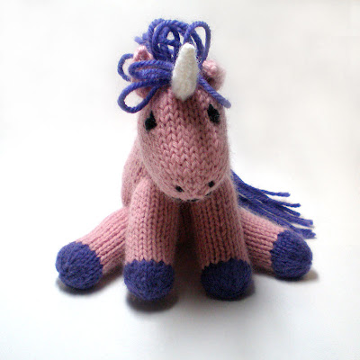 A knitted pink grumpy unicorn called Hubert