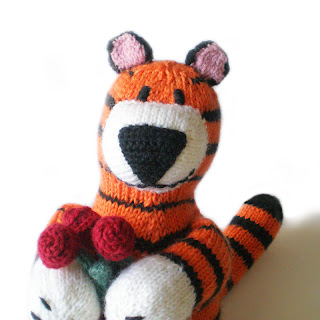 knitted tiger plushie toy Paulo holding a bouquet of red roses