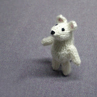 a white knitted and crocheted tiny mouse magnet