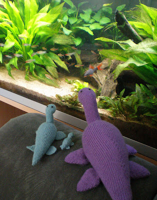 knitted nessie plesiosaurs in turquoise and purple by an aquarium