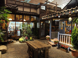 はまもと荘の中庭と波美の父親のカフェ
