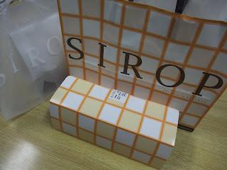 パティスリー・シロ・デラブル(Patisserie de ESAKA SIROP D'ERABLE)のチェックの紙の手提げ袋とロールケーキの箱