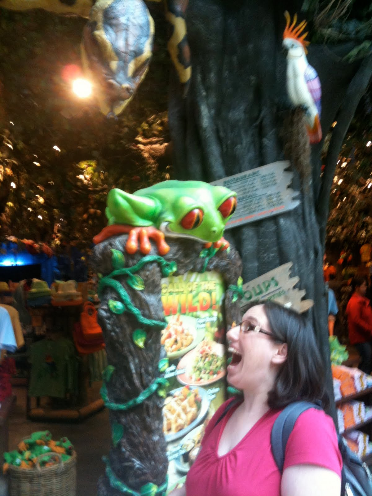 This is me being goofy just outside the Rainforest Cafe. I'm supposed to be  looking scared of the big snake in the tree, but it looks like I'm being  scared ...