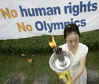 A female activists holds up a torch, its flame a symbol for universal human rights, during an
