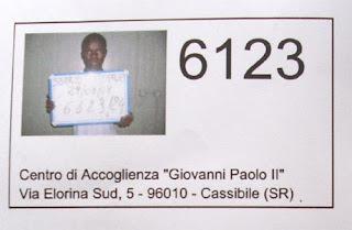 Richiedente asilo identificato con un numero all'ingresso nel Cara di Cassibile