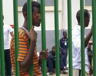 Richiedente asilo somalo appoggiato alla gabbia che circonda il Cara di Cassibile