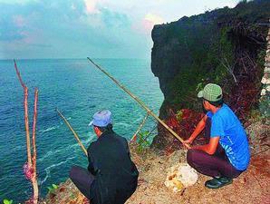Pemandu pemancing di Gunung Kidul, DI Yogyakarta, Jumidi-kiri, dan pemancing dari Jakarta yang dia dampingi tetap berjaga sekitar pukul 05.00 di Pantai Bekah, Gunung Kidul, Minggu 11.10. Pemandu disebut caddy pemancing tebing ini bisa memperoleh honor Rp 200.000 per malam.