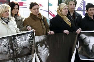 Relatives of Srebrenica victims hold photos relating to the massacre as they prepare to leave Sarajevo in Bosnia early Saturday, Feb. 24, 2007 for the Netherlands to attend Monday's verdict by the International Court of Justice in a genocide case against Serbia and Montenegro in the Hague.