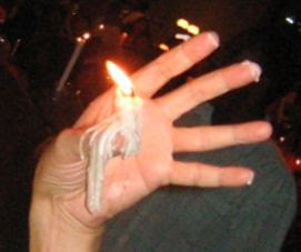lighted candle glued to thumb by resolidified melted wax
