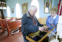 Dave Rector (left), with the Fort Pembina Historical Soceity and former Pembina mayor Hetty Walker (right), look over the Greek Orthodox Bible written in Ukrainian, that was printed in Winnipeg in 1948. St. John's Ukrainian Orthodox Church is used only for special occassions. The church building is still in the flood plain in Pembina, N.D. because it can not be moved cost effectively. Herald photo by Jackie Lorentz.