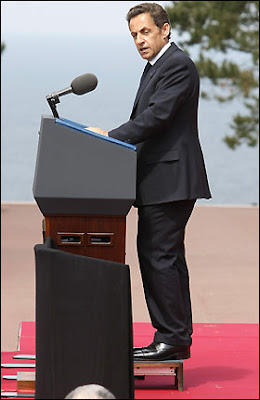 Nicolas Sarkozy on a stool at the D Day Commemoration 2009