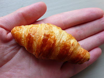 A real miniature croissant shown in a hand