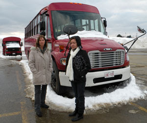 Ana Acevedo and Isabelle Hains stand in front of the 21 passenger Multi Function Activity Vehicle, November 2008