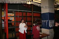 Miko en plena feina amb el omikuji (literalment loteria sagrada) o adivinació