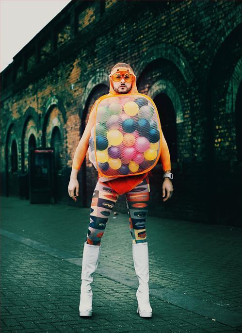 Man Wearing Mesh Sack Full of Balloons
