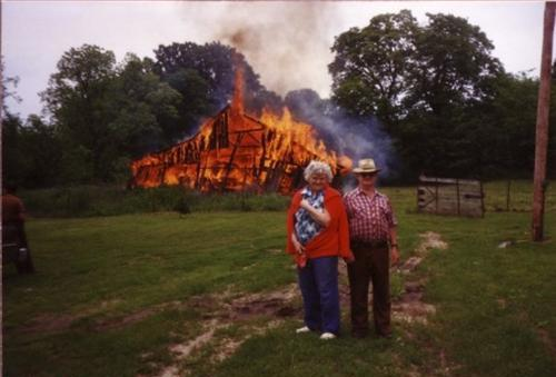 Old Couple In Front of Burning Building