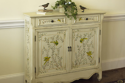 cabinet painted with birds in trees