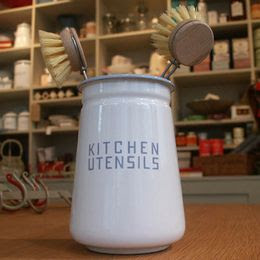 white enamel utensil holder, says kitchen utensils on it, holding scrub brushes