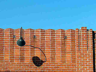 brick building facade with light fixture shadow (c)David Ocker