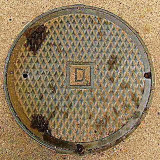 Sewer Man Hole Cover with letter D (c) David Ocker
