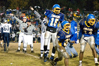 Thornton Watson (15), Ricky Denning (31) and Ronald Moore (14) celebrate the Trojan recovery