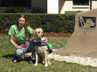 Picture of Toby & I beside the SEGDI sign - Toby's wearing his harness & coat in a sit