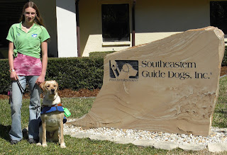 Photo of Toby & I with the SEGDI sign, an engraved rock that says Southeastern Guide Dogs, Inc. With their logo to the side. I'm wearing my green puppy raiser shirt