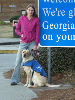 Picture of Toby and I with the Georgia sign, the sign says Welcome, We're glad Georgia's on your mind - but only some words are visible. I'm wearing jeans and a pink jacket, Toby's wearing his coat