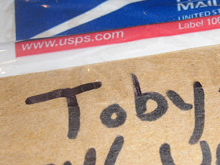 Close up picture of Toby's name on the package, it is written with a black marker