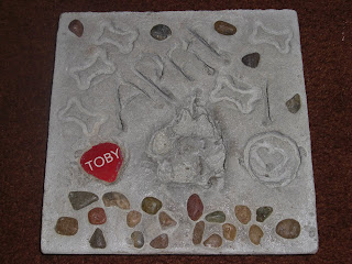 Actual picture of Toby's stone, this is when it's finished and out of the mold. It has his paw print in the middle, with his red name tag to the left, below the paw print his name is spelled out in rocks. In random places there are rocks & dog bone imprints.  It also says April 10 (2010)