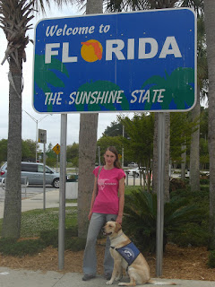 Picture of Toby & I with the Welcome To Florida sign. Toby is in a sit in coat