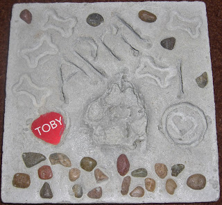 A picture of Toby's paw print stone. It says April 10 (2010). And has Toby's name spelled out in rocks